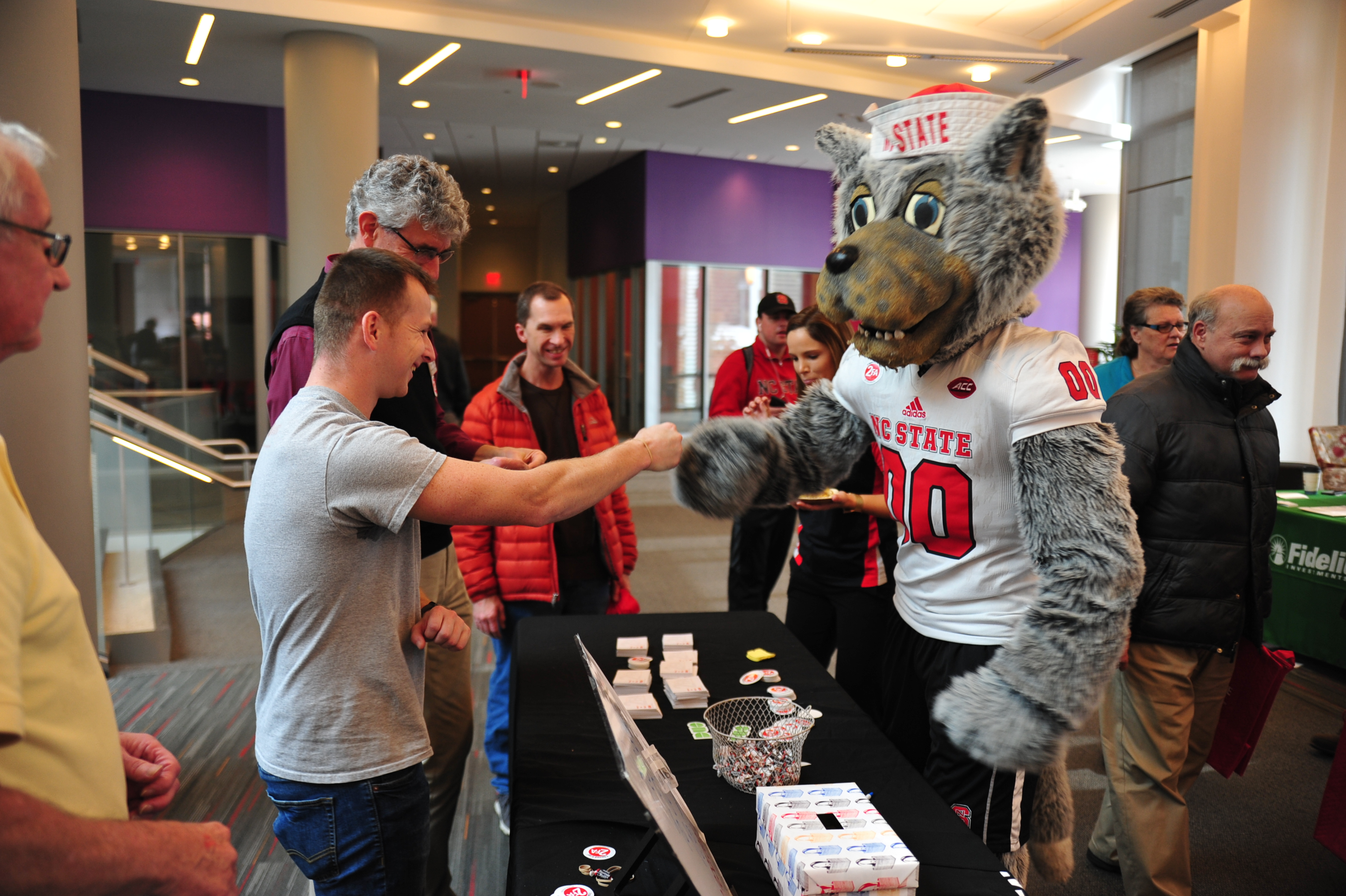 Chris Deaton fitst-bumps an NC State mascot.