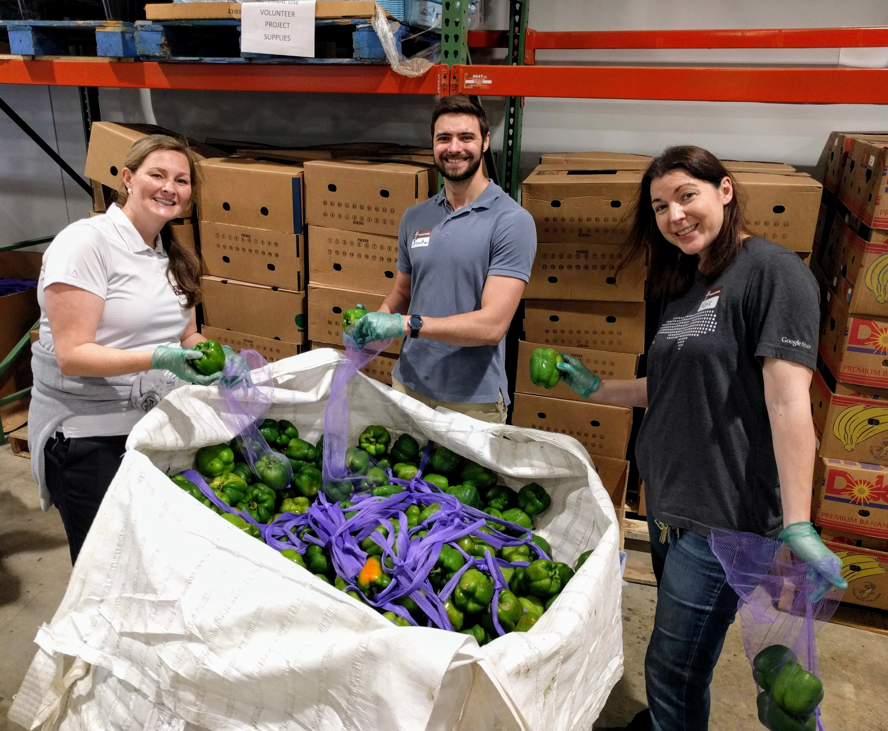 OIT staff stand next to a large bag of produce at the Food Bank of Central and Eastern North Carolina.