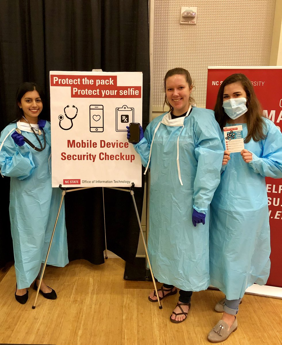 """OIT staff wear surgical garb and stand in front of a sign that reads, """"Mobile Device Security Checkup."""""""