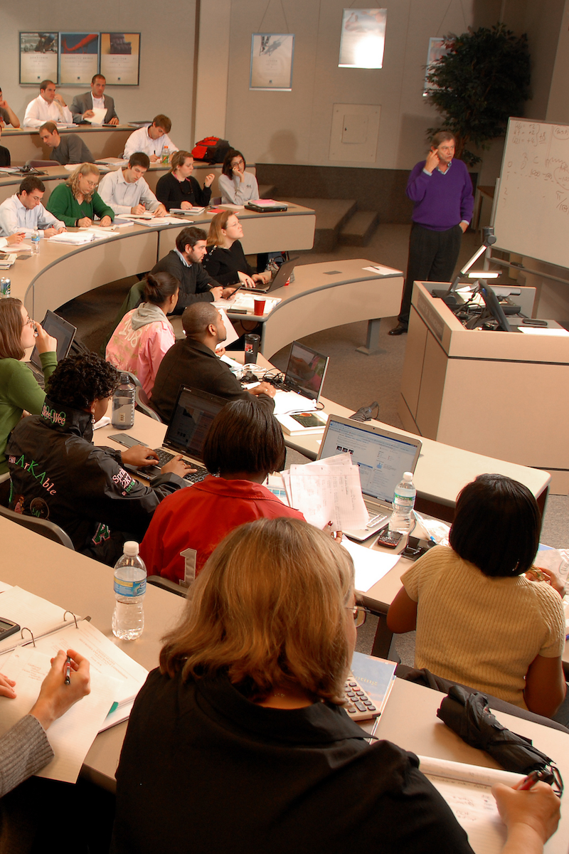 An instructor lectures in front of students in a classroom.