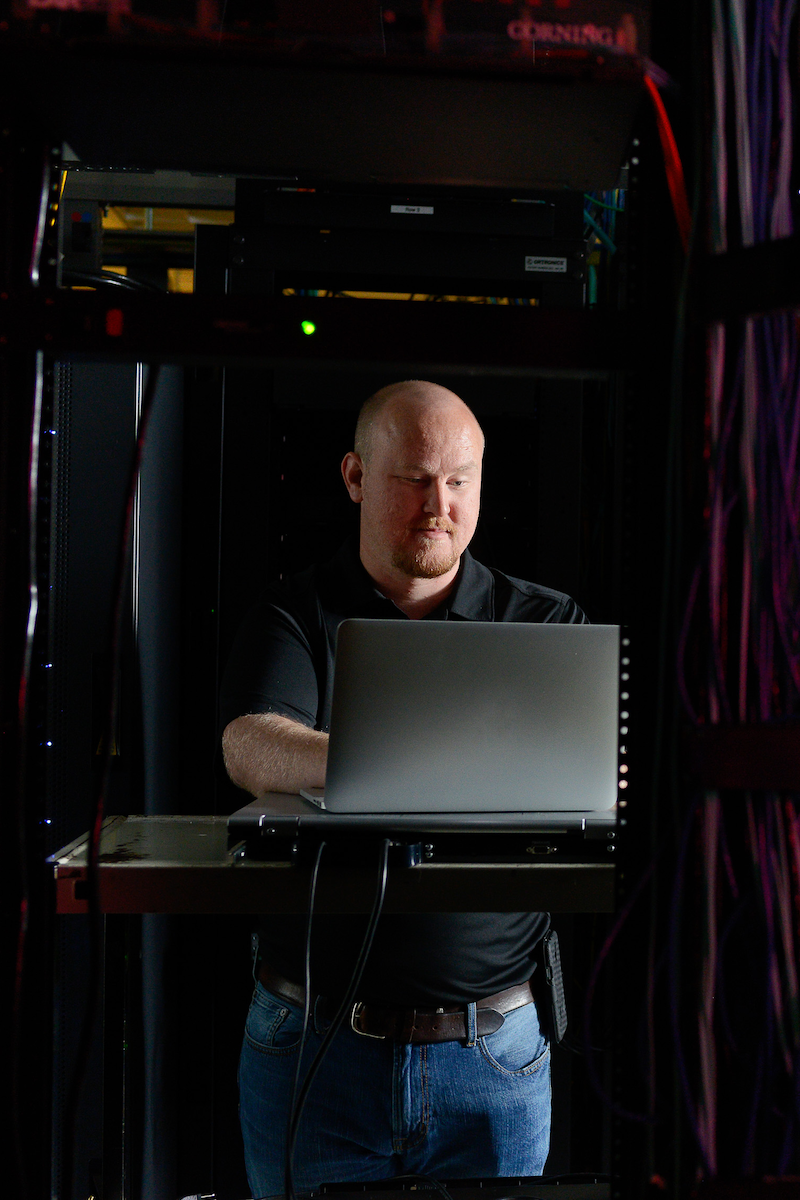 A man works at a laptop, surrounded by servers.