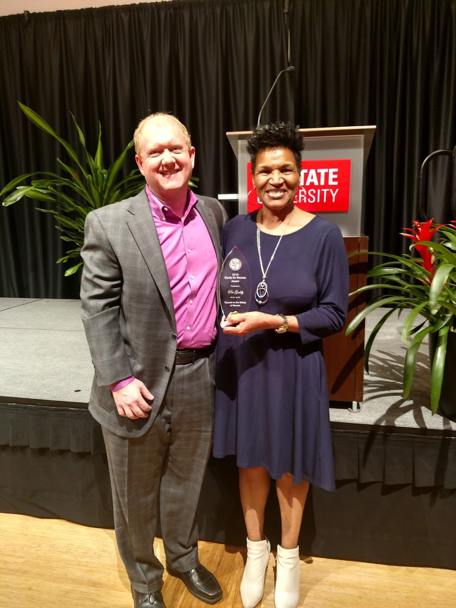 Pat Gaddy holds an award, standing with Greg Sparks.