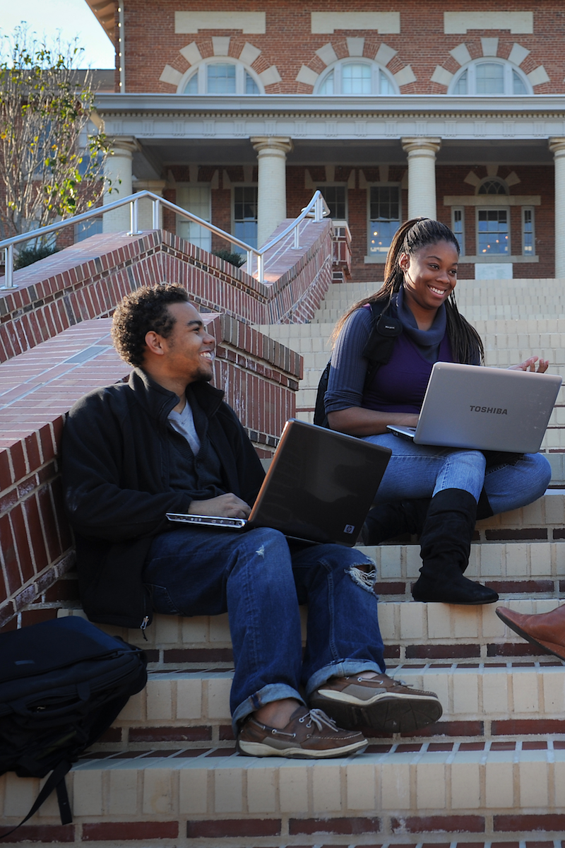 Students with laptops sit on outdoor steps.
