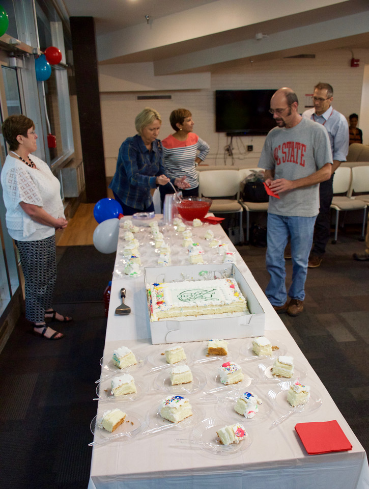 OIT staff celebrate a completed wireless upgrade with cake.