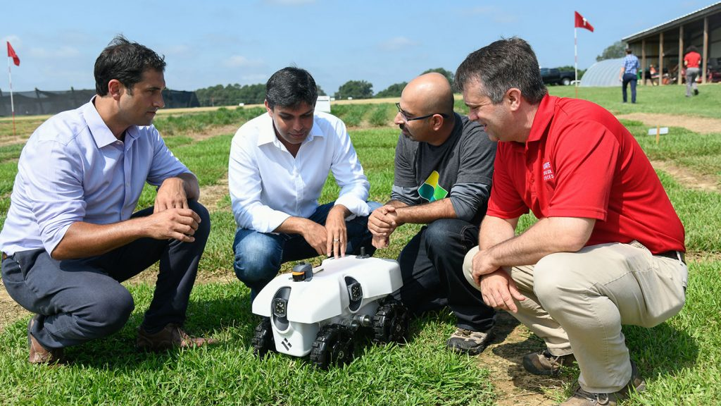 Researchers examine an autonomous agricultural data collection robot
